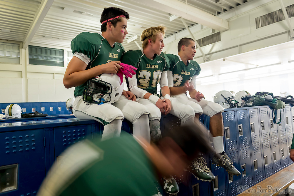 Rio Americano Raiders Hunter McGann (45), Andrew Luippold (30), and Ross Fuentes (24), sit on top of the lockers as they get ready inside the locker room before the game as the El Camino Eagles host the Rio Americano Raiders at Del Campo High School, Friday Oct 7, 2016. <br /> photo by Brian Baer