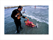 A violinist from the Doerr family with his grand-daughter in the surf after the Gypsy procession arrives at the seashore, Camargue, France May 1996..Roma Gypsies left Rajasthan in India a thousand years ago, in the ninth and tenth centuries. They were pushed west by the Ottoman Muslim Empire as it moved through Persia towards the frontiers of Europe. They entered Europe in the foutrteenth century and were slaves in Romania and Moldavia until the mid 1850s. There are about 15 million Roma gypries in the world, about 12 million who live in Europe. they are Europe's largest ethnic minority. They have rich traditions and culture, their own language. They are renowned for their prowess in music and dance; they are also skilled craftsman, metal roofmakers, silver and goldsmiths. Their traveling and nomadic lifestyle which grew from a necessity to find work, and because they were often moved on from one place to the next, has given them both a liberty but also marks them as different and they are often feared by sedentary peoples, who label and scapegoat them. They are hardy survivors and live in the brunt of racism and prejudice, often marginalised, living in poverty, without proper human rights afforded to them..