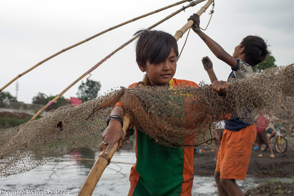 A boy folds his net after fishing in the Citarum river near Cikarees, Bale Endah district, Bandung regency, Indonesia. <br /> <br /> The Citarum river, which runs about 270 kilometers through the province of West Java, is considered to be among the world's dirtiest. Over the last twenty years, the river has been severely polluted by toxic industrial waste, trash and raw sewage. The Citarum is one of the main sources of freshwater for West Java and supplies about 80% of water for Indonesia's capital Jakarta.