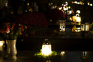 Candles on graves at the Rakowicki cemetery in Krakow at night, Poland in 2019.