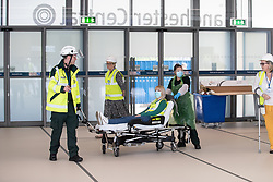 © Licensed to London News Pictures. 11/04/2020. Manchester, UK. An exercise to review the patient route from referring hospital to initial assessment at Nightingale NW is executed , with Director of Estates and Facilities at Nightingale NW , JO WRIGHT (37) , playing the patient role . The National Health Service is building a 648 bed field hospital for the treatment of Covid-19 patients , at the historical railway station terminus which now forms the main hall of the Manchester Central Convention Centre . The facility is due to open on Easter Monday , 13th April 2020 , and will treat patients from across the North West of England , providing them with general medical care and oxygen therapy after discharge from Intensive Care Units . Photo credit: Joel Goodman/LNP