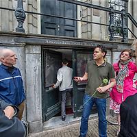 Nederland, Amsterdam, 18 mei 2017.<br /> fietstocht kamerplant tour. Een initiatief van kunstenares Tinkebell en financieel journalist Arno Wellens om de brievenbusfirma's in Nederland in het daglicht te zetten.<br /> De fietstocht voor geïnteresseerden start tegenover de Nederlandsche Bank en gaat uiteindelijk via de stad naar de Zuidas. Ondertussen wordt er door brievenbussen gegluurd en vertelt Arno Wellens alles over de brievenbusfirma's met hun kamerplantkantoortjes in Amsterdam. 1 kantoor zou liefst 10.000 van deze firma's huisvesten.<br /> Op de foto: Arno Wellens geeft uitleg voor Amsterdam Kredietbank aan de Herengracht terwijl een medewerker naar binnen glipt.<br /> <br /> <br /> Foto: Jean-Pierre Jans