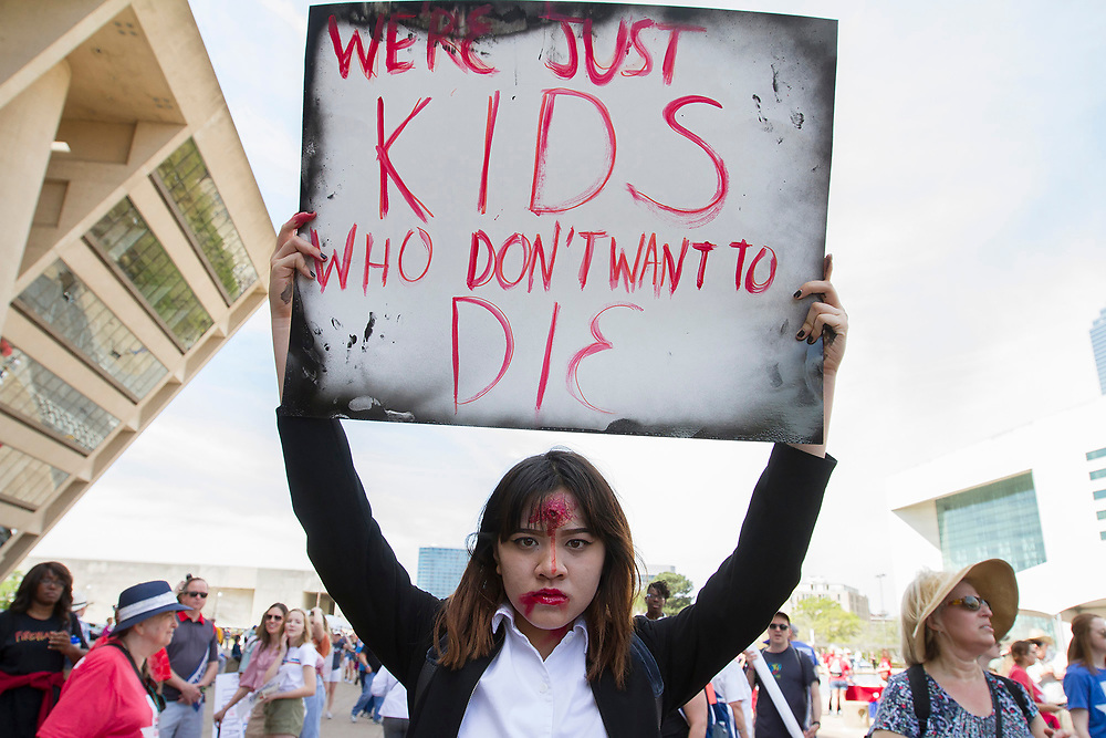 Jac Nguyen, 17, of Mansfield, Texas holds up a sign in protest during the March for Our Lives in front of Dallas City Hall in downtown Dallas.