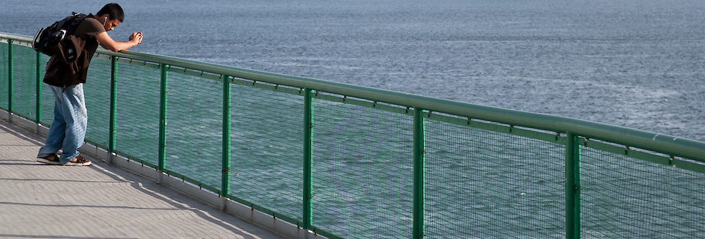 A young man relaxes while listening to music on earbuds outside on a Washington State Ferry in Rich Passage on a Puget Sound crossing enjoying pleasant weather. panorama