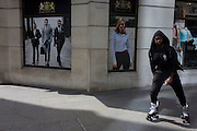 Man on skates glides past a stylish clothing shop for business people on a poster in the City of London.