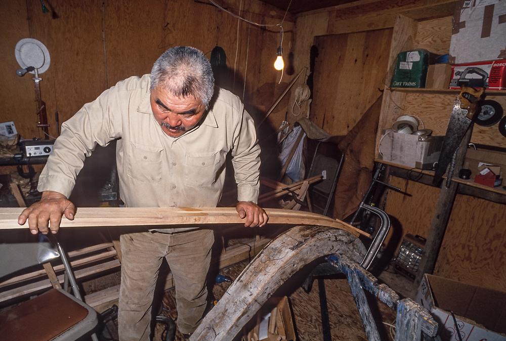 Don Smith bends a wooden ski for a cargo sled, Don's Sled Shop, Kiana, Alaska, USA