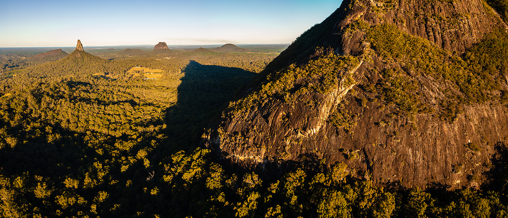 Panoramic aerial view of Mt Beerwah (foreground), and left to right in distance: Mt Ngungun, Mt Coonowrin, Mt Cooee & Mt Tibrogargan, Glass House Mountains, Sunshine Coast, Queensland, Australia