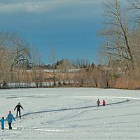 A family skates on a frozen pond near Bozeman, Montana.