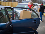 "06 APRIL 2020 - DES MOINES, IOWA: Volunteers put food into cars during a drive through emergency food distribution at First DSM Church in Des Moines. Volunteers brought food to the people in the cars to maintain proper ""social distancing."" On Monday, 06 April, Iowa reported 946 confirmed cases of the Novel Coronavirus (SARS-CoV-2) and COVID-19. There have been 25 deaths attributed to COVID-19 in Iowa. Most non-essential businesses are closed until 30 April. Well over 100,000 Iowans filed first time claims for unemployment in the last three weeks, more than applied during the peak of the Great Recession of 2008. Local food banks have seen an equal spike in people seeking nutritional assistance. First DSM Church has increased their food pantry from one day weekly to three days per week. Hundreds of people lined up Monday to get a box of food and one roll of toilet paper at the church's drive through pantry.          PHOTO BY JACK KURTZ"
