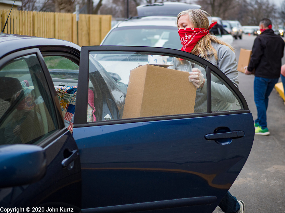 """06 APRIL 2020 - DES MOINES, IOWA: Volunteers put food into cars during a drive through emergency food distribution at First DSM Church in Des Moines. Volunteers brought food to the people in the cars to maintain proper """"social distancing."""" On Monday, 06 April, Iowa reported 946 confirmed cases of the Novel Coronavirus (SARS-CoV-2) and COVID-19. There have been 25 deaths attributed to COVID-19 in Iowa. Most non-essential businesses are closed until 30 April. Well over 100,000 Iowans filed first time claims for unemployment in the last three weeks, more than applied during the peak of the Great Recession of 2008. Local food banks have seen an equal spike in people seeking nutritional assistance. First DSM Church has increased their food pantry from one day weekly to three days per week. Hundreds of people lined up Monday to get a box of food and one roll of toilet paper at the church's drive through pantry.          PHOTO BY JACK KURTZ"""