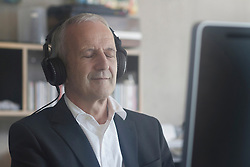 Senior businessman listening to music with headphones in the office, Freiburg im Breisgau, Baden-Wuerttemberg, Germany