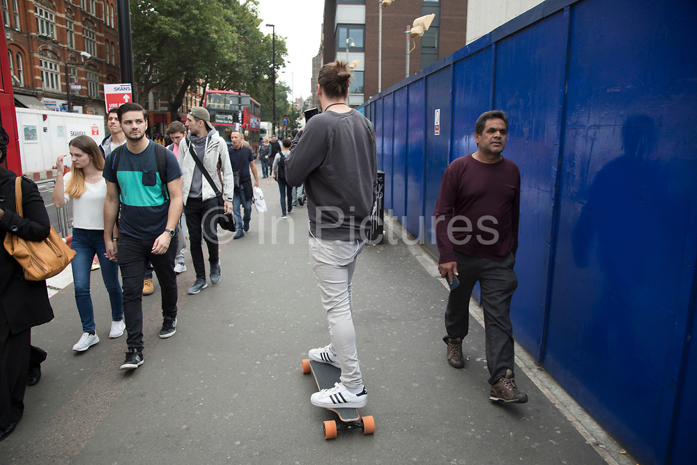 Pedestrians and a skateboarder share the pavement in central London, England, United Kingdom.