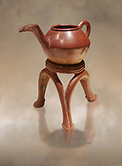 Terra cotta Hittite beaker shaped side spouted teapot and three legged stand - 1700 BC to 1500BC - Kültepe Kanesh - Museum of Anatolian Civilisations, Ankara, Turkey,  Against a warm art  background .<br /> <br /> If you prefer to buy from our ALAMY STOCK LIBRARY page at https://www.alamy.com/portfolio/paul-williams-funkystock/hittite-art-antiquities.html  - Type Kultepe  into the LOWER SEARCH WITHIN GALLERY box. Refine search by adding background colour, place, museum etc<br /> <br /> Visit our HITTITE PHOTO COLLECTIONS for more photos to download or buy as wall art prints https://funkystock.photoshelter.com/gallery-collection/The-Hittites-Art-Artefacts-Antiquities-Historic-Sites-Pictures-Images-of/C0000NUBSMhSc3Oo