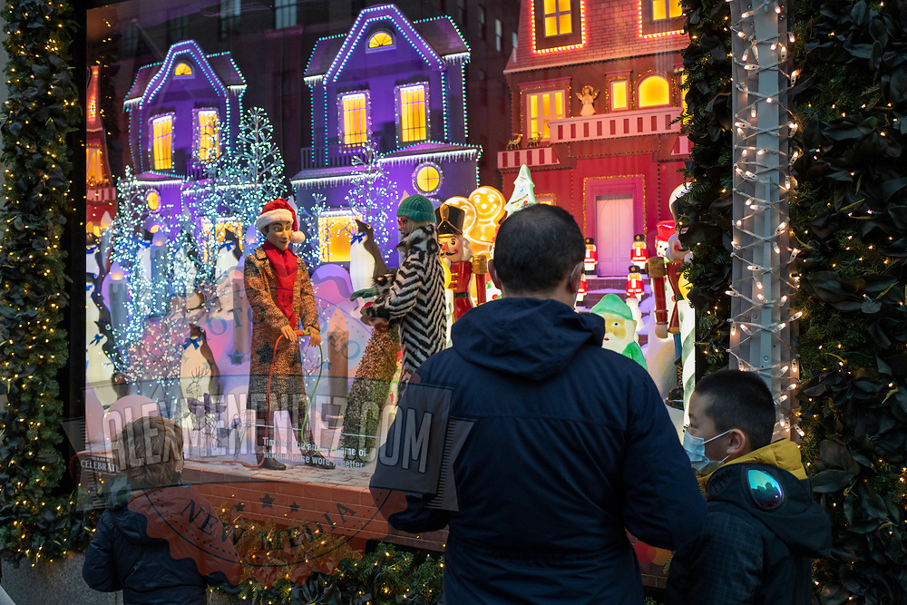 Shoppers and visitors walk down 5th Avenue and stop to look at the Saks 5th Avenue window displays for the Holiday season during the Coronavirus (Covid-19) outbreak in Manhattan,New York on Sunday, December 6, 2020. (Alex Menendez via AP)