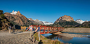"""Rio Electrico bridge and trailhead on gravel road RP23 between El Chalten & Lago del Desierto, in Santa Cruz Province, Argentina, Patagonia, South America. We hiked the scenic Rio Electrico Valley to Refugio Piedra del Fraile (""""Stone of the Friar"""", 14.5 km round trip). From the refuge, a rewarding day hike visits Lago Pollone (8.5 km round trip with 320 m gain) beneath towering Cerro Fitz Roy and Aguja Pollone. Another path from the refuge ascends very steeply to Paso Quadrado (gaining 1340 m vertically in 8.4 km round trip) for a spectacular view south to Guillaumet, Mermoz, Fitz Roy, Cerro Torre, and Aguja Pollone (left to right). The last kilometer climbs up steep snow which could require crampons if icy. Views keep improving the higher you go. This image was stitched from multiple overlapping photos."""
