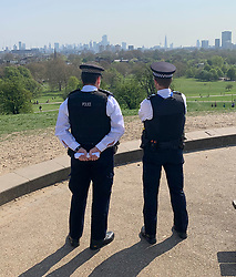 © Licensed to London News Pictures. 11/04/2020. London, UK. Police officers watch out from on top of Primrose Hill in London, during a pandemic outbreak of the Coronavirus COVID-19 disease. The public have been told they can only leave their homes when absolutely essential, in an attempt to fight the spread of coronavirus COVID-19 disease. Photo credit: Ben Cawthra/LNP