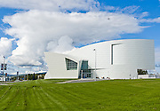 Dramatic architecture and distinctive exhibit galleries make the Museum of the North a must-see destination at the University of Alaska, in Fairbanks, Alaska, USA. An anvil shaped cumulonimbus cloud towers over the gracefully shaped white museum and its expansive green lawn.