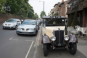 Vintage car parked outside a cafe in South London, England, United Kingdom. The vehicle is an old delivery van and is being used to entice customers into the establishment it is outside.