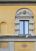 Architectural detail of a window with a broken pediment in the orange and brown ministry buildings surrounding Skanderbeg Square. Tirana, Albania.