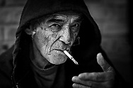 Close up of a man who is living on the streets, smoking a cigarette