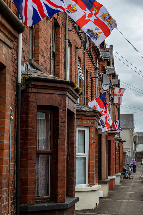 Terraced street. Flags flying ahead of the famous Orange March, Belfast, NI, 2021