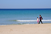 Israel. Haifa, Dado Beach, mother and daughter stroll on the beach - Model release Available