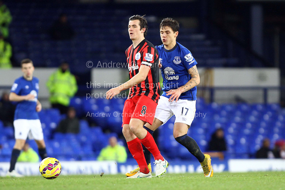 Joey Barton of Queens Park Rangers passes under pressure from Muhamed Besic of Everton. Barclays Premier league match, Everton v Queens Park Rangers at Goodison Park in Liverpool, Merseyside on Monday 15th December 2014.<br /> pic by Chris Stading, Andrew Orchard sports photography.