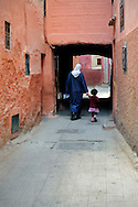 Morocco, Marrakesh. Woman and her little daughter walking the narrow street of the pink medina in Marrakesh.
