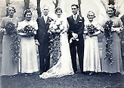 groom, bride, bridesmaids and father of the bride vintage group portrait