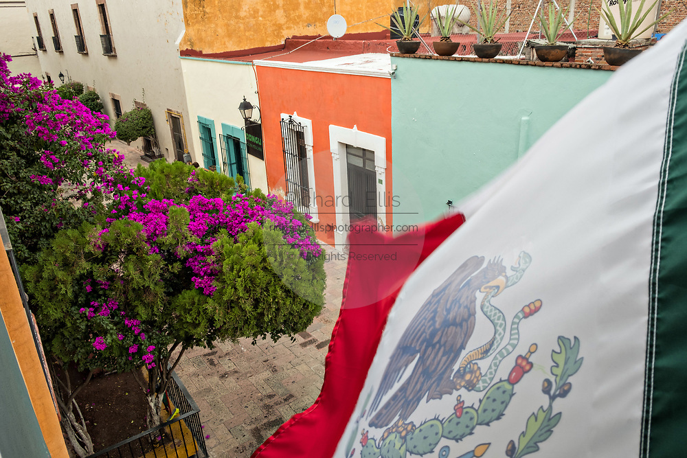 The Mexican flag flies over a colorful alley in the old colonial section of Santiago de Queretaro, Queretaro State, Mexico.