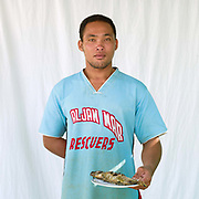 Romel Landao (28), fisherman with a freshly cooked fish, Pooc, Bantayan Island, The Philippines. Every morning at 7 am fisherwomen meet fishermen as they return from the sea with their catch. Women sort the fish by size and type, then weigh and distribute the fish between saleswomen to be sold on to local customers. On November 6 2013 Typhoon Haiyan hit the Philippines and was one of the most powerful storms to ever make landfall.  Three-quarters of the island's population of about 136,000 depend on fishing as their main source of income. Thousands lost their boats and equipment in the storm. Oxfam is working to support the immediate and long-term needs of affected communities on Bantayan Island.