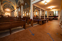 Directional arrows assist parishioners to their seats inside Sacred Heart Church to comply with social distancing guidelines.  (Karen Bobotas/for the Laconia Daily Sun)