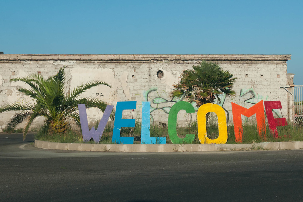 A coloured 'Welcome' sign is seen near an illegal migrant camp on August 03, 2017 in Crotone, Italy.  The city of Crotone hosts one of the biggest european centre for migrants, but some of them live in clandestinity, even for two years, in an area near the city railway station, because they are afraid to be rejected and to be sent to their nations again. ©Simone Padovani