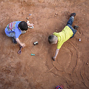 Two young boys create their own tracks for their toy cars in the dirt on a Saturday night during a stock car race in The Carolinas. ©Travis Bell Photography