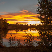 Lenticular clouds glow in a sunset over a pond in Montana's Gallatin Valley, near Bozeman.