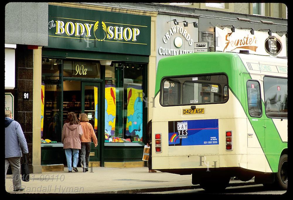 Two young women enter The Body Shop as city bus stops along Princes Street in Edinburgh. Scotland