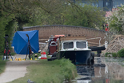 © Licensed to London News Pictures. 27/04/2021. Aylesbury, UK. Evidence markers on a pathway next to a boat following a fatal assault near Bridge 14 on the Grand Union Canal near Broughton in Aylesbury at about 12.20pm on Monday 26/04)/2021. Police officers found a man with serious injuries and despite the efforts of emergency services the man died at the scene. Photo credit: Peter Manning/LNP