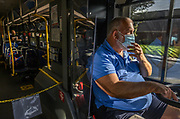 Sacramento Regional Transit driver Steve Robison touches his mask as he drives during his routine bus route in his bus in Sacramento on Monday, April 27, 2020. Robison is one of dozens of Sacramento Regional Transit bus drivers and light rail train operators who signed up for shifts during the coronavirus outbreak.