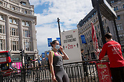 With a further 89 UK covid victims in the last 24hrs, bringing the total victims to 43,995 during the Coronavirus pandemic, shops continue opening along London's Oxford Street where social distance and hygiene advice towers are located at the only entrance to the underground station, where shoppers and users of public transport observe restriction rules by putting on face masks, on 2nd July 2020, in London, England.