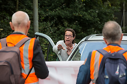 Godstone, UK. 13th September, 2021. A motorist contests Insulate Britain climate activists blocking a slip road from the M25, causing a long tailback on the motorway, as part of a new campaign intended to push the UK government to make significant legislative change to start lowering emissions. The activists, who wrote to Prime Minister Boris Johnson on 13th August, are demanding that the government immediately promises both to fully fund and ensure the insulation of all social housing in Britain by 2025 and to produce within four months a legally binding national plan to fully fund and ensure the full low-energy and low-carbon whole-house retrofit, with no externalised costs, of all homes in Britain by 2030 as part of a just transition to full decarbonisation of all parts of society and the economy.