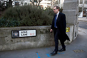 City worker passes sign for Love Lane in the City of London.