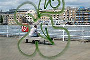 Surrounded by the swirl of sprayed graffiti, a man sits reading on a bench overlooking the Thames river, at Butlers Wharf, on 11th June 2021, in London, England.