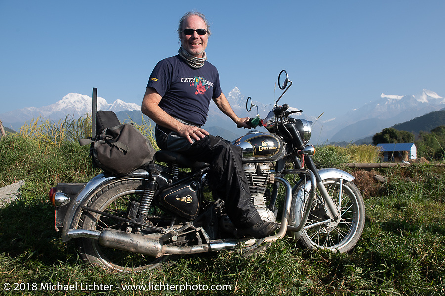 Jonathan Pite poses with a spectacular background of 23,000' peaks on day-4 our our Himalayan Heroes adventure riding from Pokhara to Kalopani, Nepal. Friday, November 9, 2018. Photography ©2018 Michael Lichter.