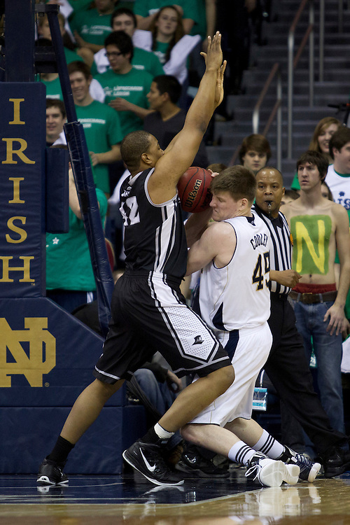 Notre Dame forward Jack Cooley (#45) attempts to shoot the ball as Providence center Bilal Dixon (#42) defends in first half action of NCAA Men's basketball game between Providence and Notre Dame.  The Notre Dame Fighting Irish defeated the Providence Friars 75-69 in game at Purcell Pavilion at the Joyce Center in South Bend, Indiana.