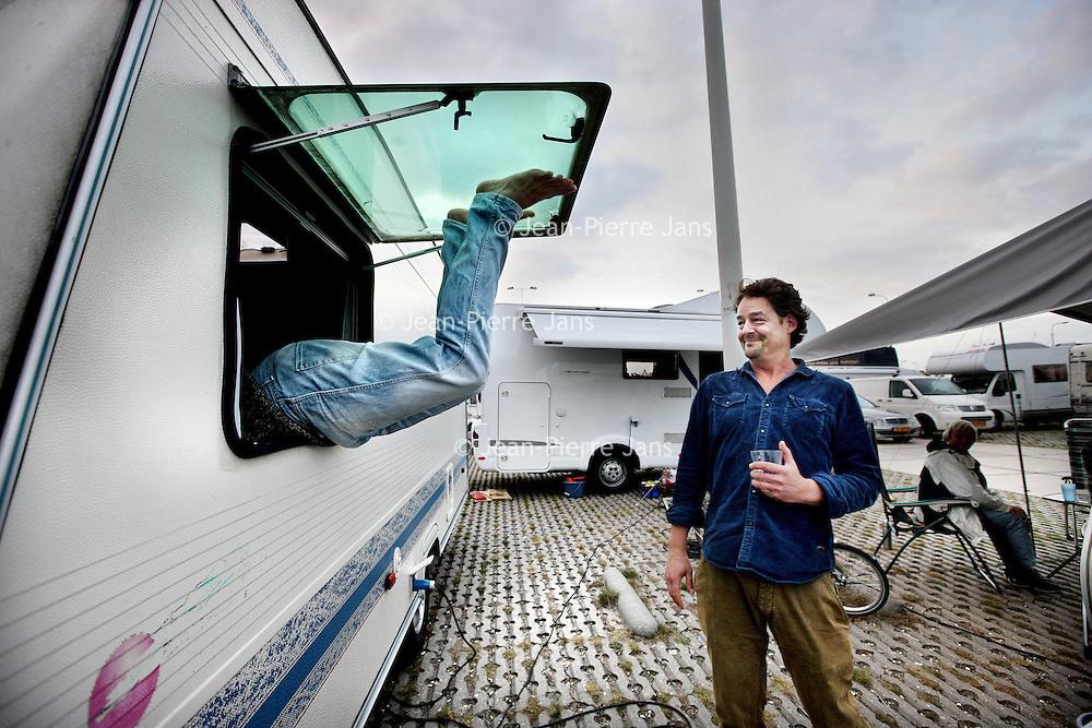 Nederland, Amsterdam , 1 oktober 2014.<br /> De rij caravans met mensen die een zelfbouwkavel willen kopen op het Zeeburgereiland wordt steeds groter.<br /> Sommige staan al een paar weken in de wachtrij totdat ze een kavel mogen kopen. Pas volgende week zaterdag gaan de kavels pas in de verkoop, maar wie weg gaat, verliest zijn plek in de rij.<br /> Een van de kampeerders staat er al een tijdje in zijn caravan: 'Ik ben hier behoorlijk vroeg gaan staan, want er is één kavel waar ik echt geïntresseerd in ben. Er hoeft er maar een eerder te zijn en dan ben je 'm kwijt.'<br /> De wachtende kopers vinden het best gezellig op het terrein: 'Je ontmoet een soort van je toekomstige buren als het zo doorgaat. Dat geeft een apart campinggevoel en we barbecuen samen.'<br /> Een probleempje, als je weggaat ben je je plek kwijt. 'Als je moet werken moet je zorgen dat er iemand anders op je plek zit. Ik had hier eerst helemaal geen zin in, maar het is toch wel een bizar avontuur.'<br /> Op de foto: 1 van de potentiele kavelkopers had zichzelf buitengesloten en klimt vervolgens weer via het raam van zijn gehuurde caravan naar binnen.<br /> Foto:Jean-Pierre Jans