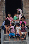 Batak family group sitting on the doorstep of their traditional home..Batak Indigenous Christian people living on Samosir Island and nearby Lake Toba in Indonesia. There are some 6 million Christian Batak in Indonesia, the world's largest Muslim country of 237 million people, which has more Muslims than any other in the world. Though it has a long history of religious tolerance, a small extremist fringe of Muslims have been more vocal and violent towards Christians in recent years. ..Batak religion is found among the Batak societies around Lake Toba in north Sumatra. It is ethnically diverse, syncretic, liable to change, and linked with village organisations and the monotheistic Indonesian culture. Toba Batak houses are boat-shaped with intricately carved gables and upsweeping roof ridges, and Karo Batak houses rise up in tiers. Both are built on piles and are derived from an ancient Dong-Son model. The gable ends of traditional houses, Rumah Bolon or Jabu, are richly decorated with the cosmic serpent Naga Padoha carved in wood or in mosaic, lizards, double spirals, female breasts, and the head of the singa, a monster with protruding eyes that is part human, part water buffalo, and part crocodile or lizard. The layout of the village symbolises the Batak cosmos. They cultivate irrigated rice and vegetables. Irrigated rice cultivation can support a large population, and the Toba and the Karo live in densely clustered villages, which are limited to around ten homes to save farming land. The kinship system is based on marriage alliances linking lineages of patrilineal clans called marga. In the 1820's Islam came to the southern Angkola and Mandailing homelands, and in the 1850's and 1860's Christianity arrived in the Angkola and Toba region with Dutch missionaries and the German Rheinische Mission Gesellschaft. The first German missionary caused the Dutch to stop Batak communal sacrificial rituals and music, which was a major blow to the traditional religion. Dutch colo