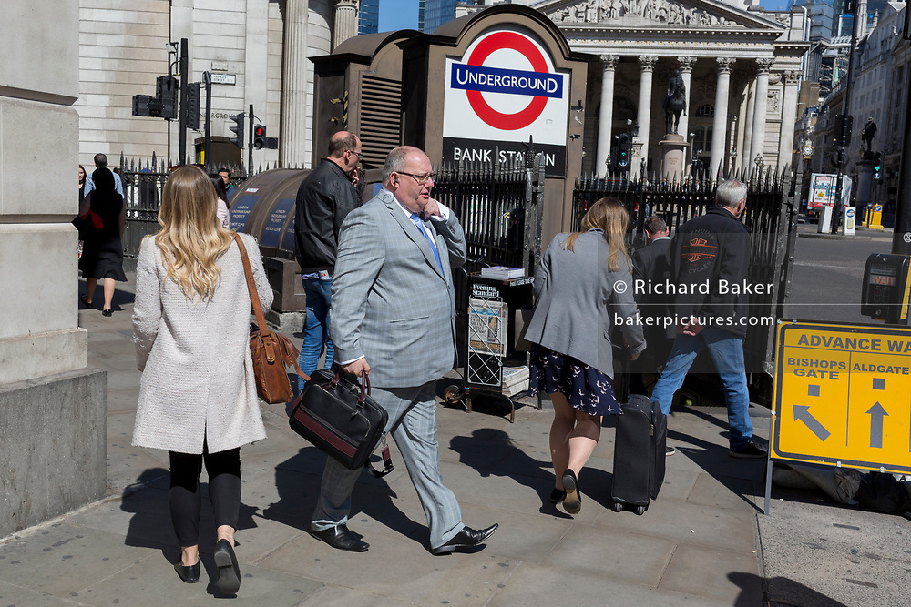 A large middle-aged businessman wearing a silver suit walks past one entrance of Bank Underground Station in the City of London, the capital's ancient, financial district, on 14th May, in London, England.