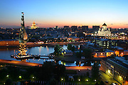 Dusk scene of Moscow with the Moscow River. On the left is a huge statue of Peter the Great on a sailing ship, and on the right is the Cathedral of Christ the Saviour.