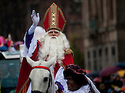 Saint Nicolas arrives during the Sinterklaas parade, Dam Square, Amsterdam, 14th November 2010. Sinterklaas, the basis for Santa Claus in other countries, arrives from Spain by boat,  accompanied by Black Peter, played by multitudes of white Dutch people in blackface - a tradition that evokes some controversy. Contrary to traditions of Santa Claus elsewhere, Sinterklass arrives by boat, then rides through the streets on his grey horse, Amerigo,  in mid-November, bringing in the Christmas season. The Zwarte Pieten (Black Peters) distribute sweets and gingerbread cookies to the crowd along the parade route.