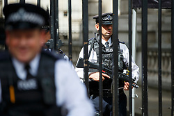 © Licensed to London News Pictures. 03/08/2016. London, UK. Armed police officers guarding Downing Street in Westminster, London on 3 August 2016. More armed police will be seen on patrol in London, Metropolitan Police commissioner Sir Bernard Hogan-Howe and Mayor of London Sadiq Khan announced. Photo credit: Tolga Akmen/LNP